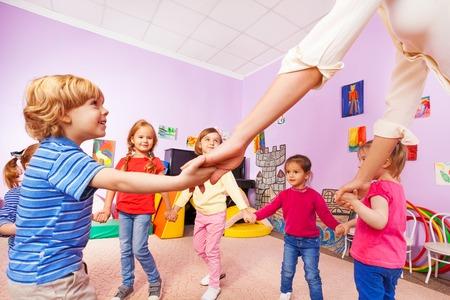 Grupo de niños y niñas jugar con estribillo con el profesor en clase de la guardería cerca vista desde abajo Foto de archivo - 50521856