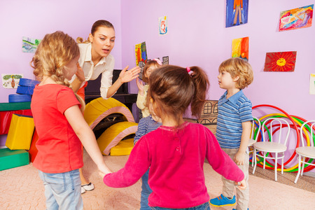 kindergarten education: Group of kids boys and girls hold stand together and clapping hands with teacher showing and giving instructions
