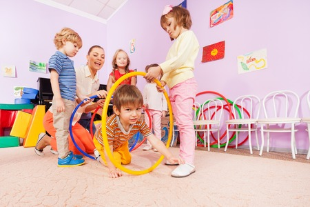 developmental: Little boy crawl though plastic hoop with other kids help holding them and under teacher instructions Stock Photo