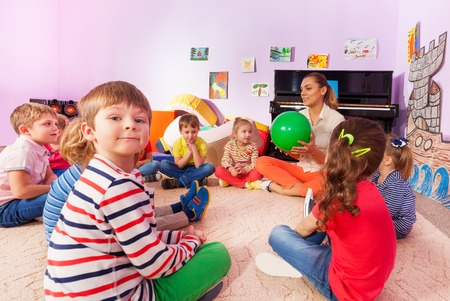 people sitting: Large group of kids boys and girls sit together in kindergarten class and play word game with ball