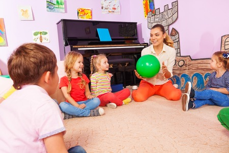 Group of kids boys and girls with teacher sit and play with ball answering questions as they go Stockfoto