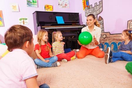 Gruppe Kinder, Jungen und Mädchen mit Lehrer sitzen und spielen mit Ball die Beantwortung von Fragen, wie sie gehen