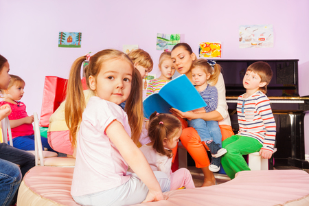 Portrait of little girl with ponytails sit among group of kids listening to teacher nurse reading book and telling stories Stock Photo