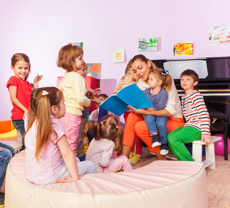Group of happy children boys and girls sit around teacher and listening to story she reads to them Foto de archivo