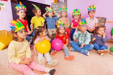 storytelling: Group of kids boys and girls sit in circle with balls and handmade headwear Stock Photo