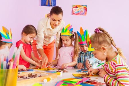 preschool children: Beautiful young teacher woman show little children boys and girls how to make glue and draw craft image in preschool class Stock Photo