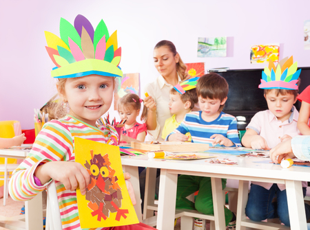 children art: Portrait of a little girls with children friends making images gluing paper with teacher helping them Stock Photo