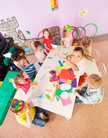 children drawing: Group of kids boys and girls sit around the table in kindergarten with teacher view from above