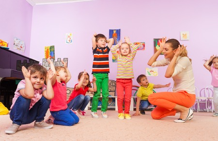 Group of kids repeat after teacher in kindergarten class holding hands making big ears Stock Photo