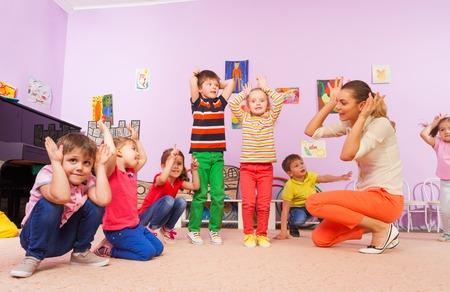 Gruppe Kinder wiederholen, nachdem Lehrer im Kindergarten Klasse halten Hände machen große Ohren