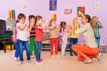 Group of kids boys and girls repeating gesture with hands playing fun game Foto de archivo