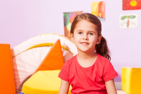 mignonne petite fille: Portrait of little girl with long hair sit in kindergarten room Banque d'images
