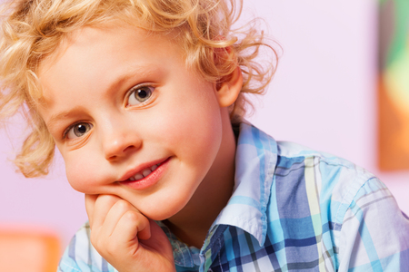 bambini pensierosi: Handsome boy portrait holding hand near chin smile and look at camera expressing positive and happy look