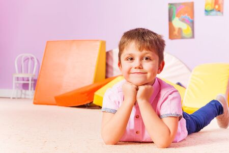 boy beautiful: Close happy portrait of a boy smiling and looking at camera laying on the floor in kindergarten room
