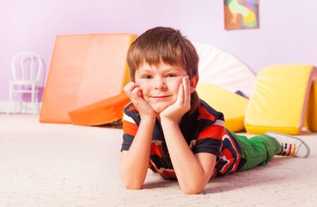 child boy: Close happy portrait of a boy smiling and looking at camera laying on the floor and holding head with hands in kindergarten room Stock Photo