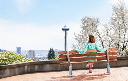 space needle: Young woman sitting on the bench and looking at Seattle downtown panorama and space needle