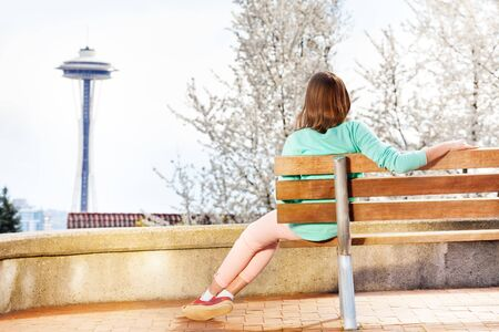 space needle: Young woman sitting on the bench and looking at Seattle space needle tower Stock Photo