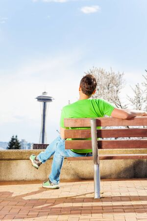 space needle: Man sitting on bench and look at Seattle downtown space needle tower