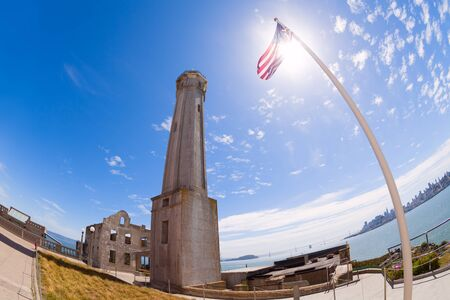 administrative buildings: US flag lighthouse and ruins of administrative buildings in San Francisco bay shot by wide angle lense Stock Photo