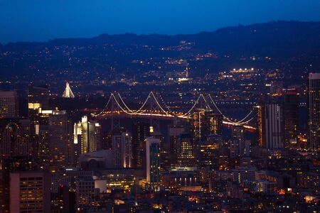 span: Oakland Bay Bridge in San Francisco during the night over city downtown