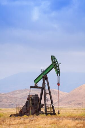 dug well: One green steel oil derrick producing deposits of oil fuel at the deserts of California Stock Photo