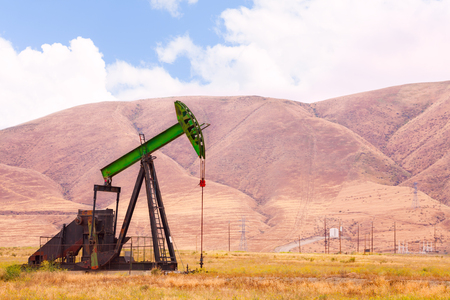 dug well: One big iron stained oil-derrick operating nearby the mountain at the cloudy day Stock Photo