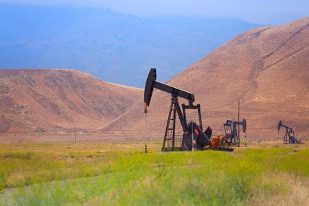 dug well: Work of oil derricks in the foothills in California Stock Photo