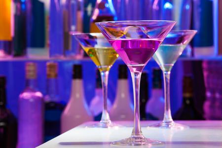 Set von drei Cocktail-Martini-Gläser in der Bar, die mit Flaschen auf dem Hintergrund Standard-Bild