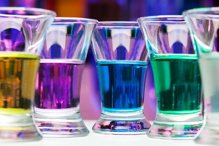 shooter drink: Closeup of shining colorful shoot drinks with alcohol standing in the bar table Stock Photo