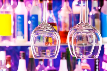 cocktail glasses: Close-up of wine glasses with the bar on background and color bottles on shelves Stock Photo