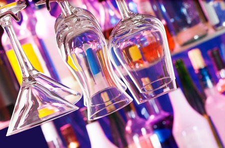 cocktail glasses: Different glasses hanging on the bar hanger, bottles on background