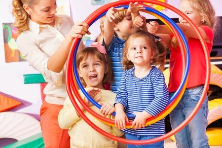 先生と少しの子供の男の子と女の子のグループに見えるプラスチック スポーツ フープの笑顔し、ポーズが