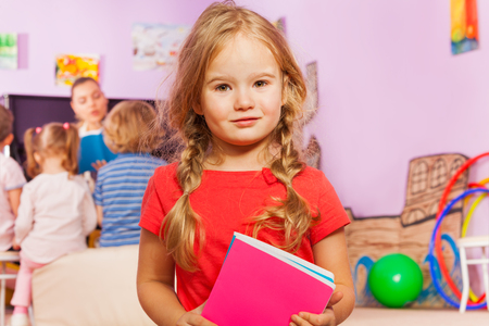 a study: Portrait of little girl in developmental class standing with books and class behind