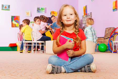 Close portrait of nice little girl sit in kindergarten class holding books and smile with group learning on background