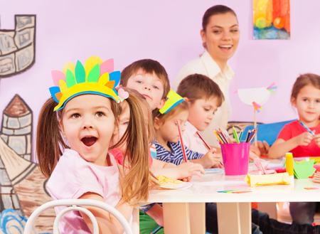art and craft: Nice little girl close-up portrait and group of kids boys and girls with teacher in early developing kindergarten class working with paper