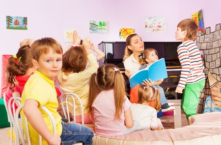 sit around: Large group of friends sit around woman reading a book and talking to boys and girls in kindergarten lesson