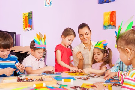 예술 유치원 클래스에서 아이들이 종이 및 판지 이미지를 접착제하도록 돕는 교사 일