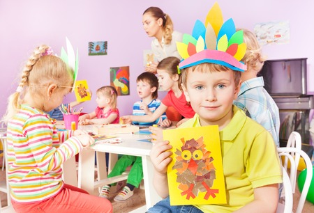 Nice little boy show paper image with his friends on background with teacher gluing paper