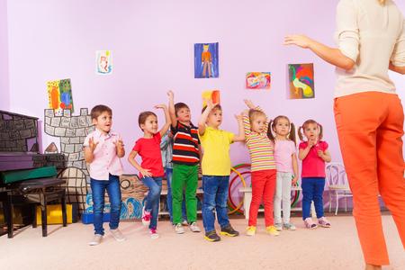Groep kinderen herhalen oefening na leraar in kleuterklas