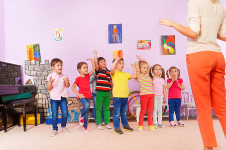 Group of kids repeating exercise after teacher in kindergarten class