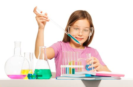 blinkers: Young girl dripping from a pipette some blue reactant from the flask at the  laboratory Stock Photo