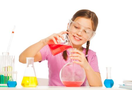 volumetric flask: One Caucasian schoolgirl pouring red liquid reactant from volumetric glass to the big flask at the laboratory desk