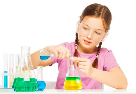 blinkers: One pretty Caucasian schoolgirl in safe eyewear mixing blue and yellow reactants in flask at the laboratory