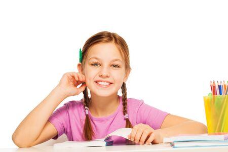 niño escuela: Una colegiala divertido va a hacer sus lecciones con el lápiz detrás de la oreja