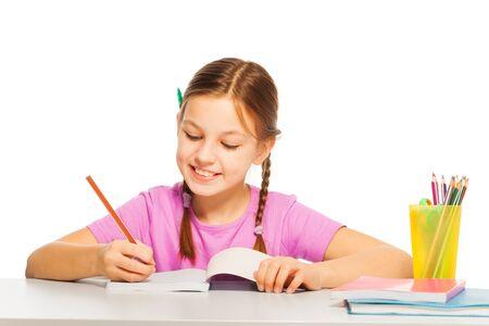 kids class: Pretty diligent schoolgirl in pink tee writing with orange pencil at school