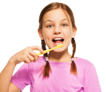 Young smiling girl with toothbrush brushing her white teeth doing her daily dental care.