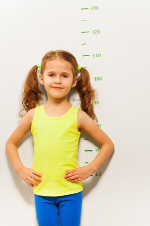 tall: Little five years old girl stand by the scale of height on the wall measuring length of 110 cm.