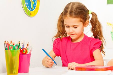 Jedna mądra uczennica piśmie z niebieskim długopisem na biurku w klasie