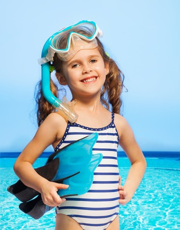 Little smiling girl wearing stripped swimwear with diving equipment against of sea and blue sky