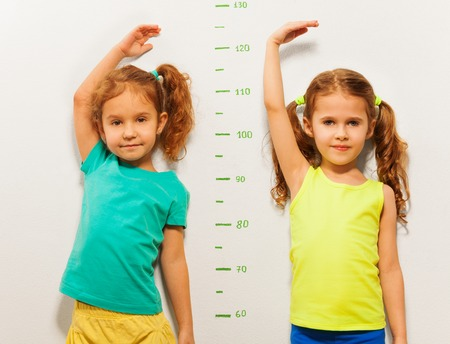 Two little girls standing close to the scale on the wall showing height with hand above the head Stock Photo